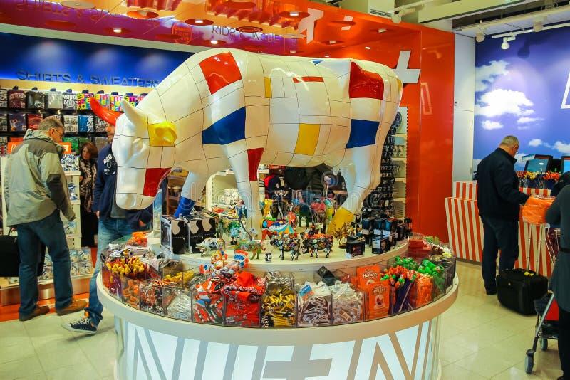 Los pasajeros están haciendo compras en la tienda de regalos en el aeropuerto Amsterda imagen de archivo