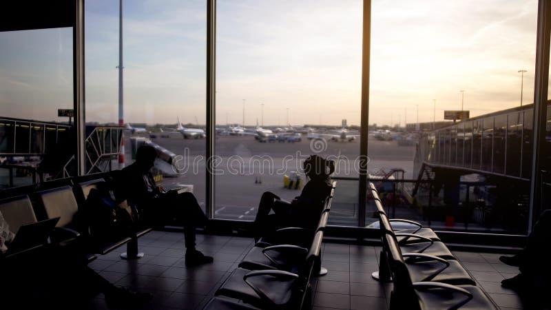 Los pasajeros masculinos y femeninos que sientan salida gandulean, esperando el avión, viaje imágenes de archivo libres de regalías