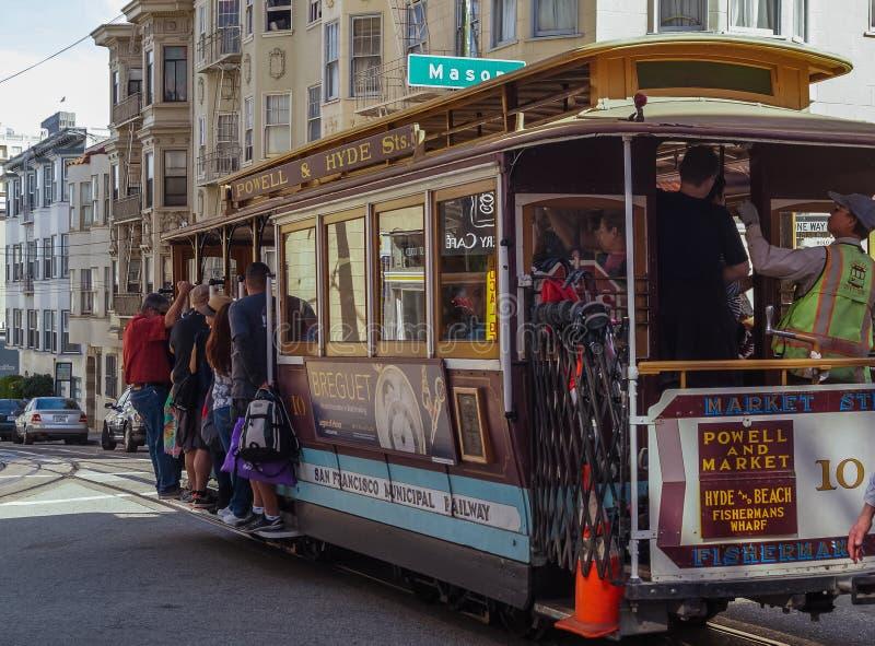 Los pasajeros montan en un teleférico en San Fransisco, los E.E.U.U. imagen de archivo libre de regalías