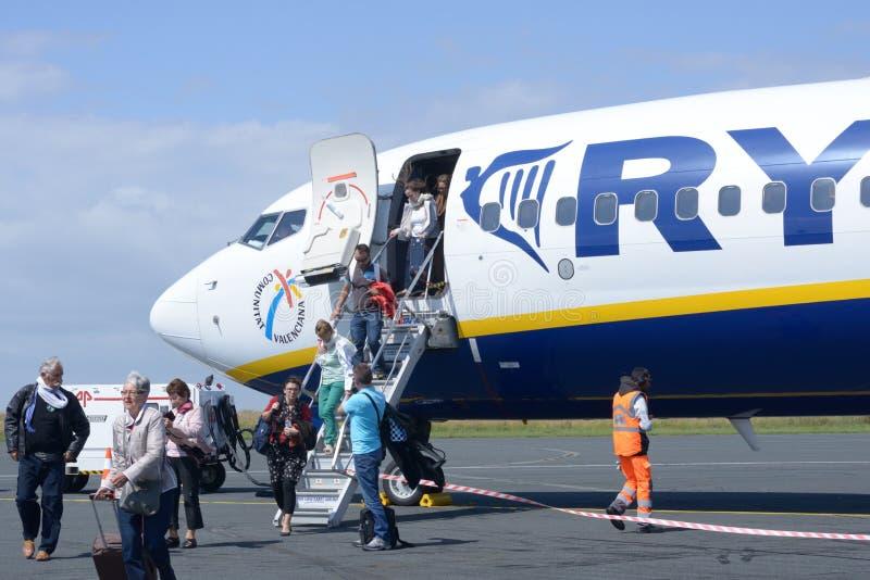 Los pasajeros salen del aeroplano fotografía de archivo