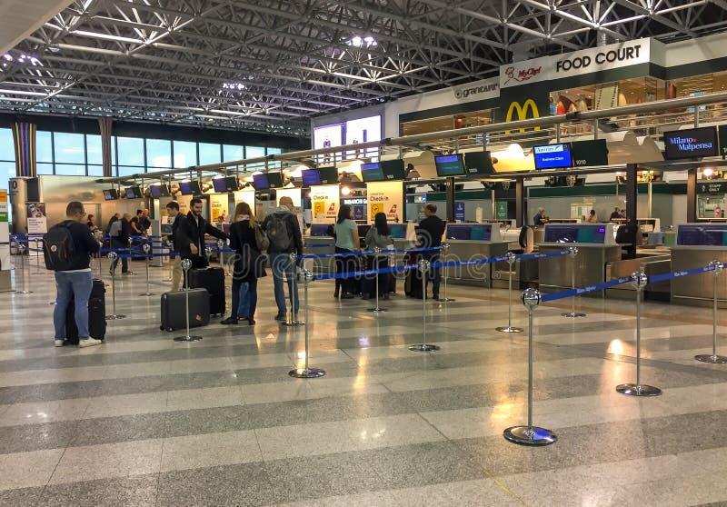 Los pasajeros se alinearon para chek-en dentro del terminal de aeropuerto de Milán-Malpensa 1 fotos de archivo libres de regalías