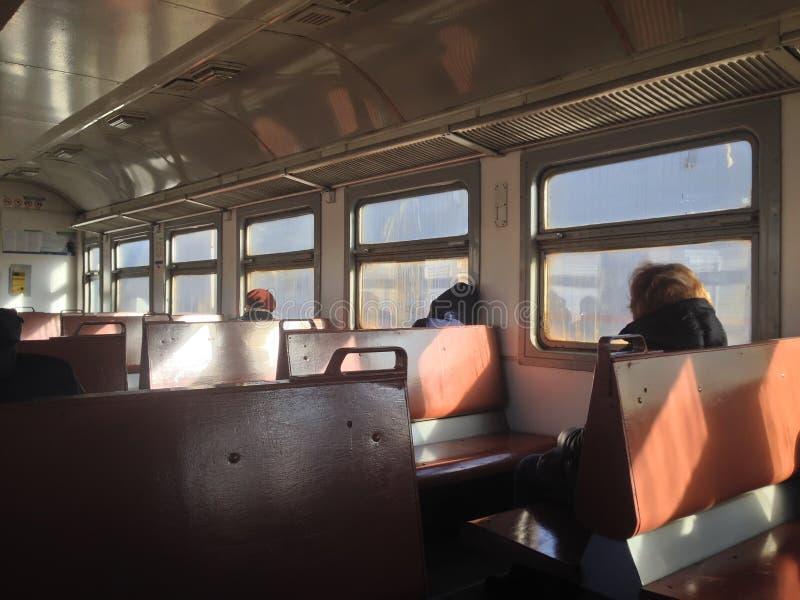 Los pasajeros se sientan por la ventana en el tren imagen de archivo