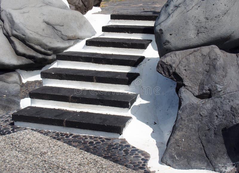 los pasos de piedra negros elegantes exteriores fijaron en el hormigón blanco imagen de archivo