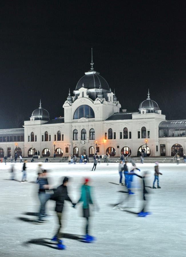 Los patinadores de hielo en ciudad estacionan la pista de hielo imagen de archivo