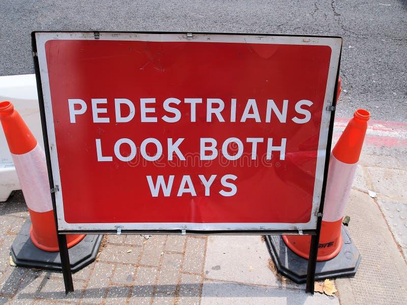 Los peatones miran ambas maneras, señal de peligro de los trabajos de la calle imagen de archivo libre de regalías