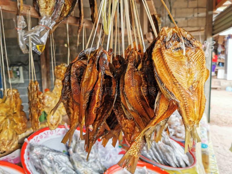 los peces en el agua dulce del interior se secaron a la luz del sol, colgados por el bambú para vender fotos de archivo
