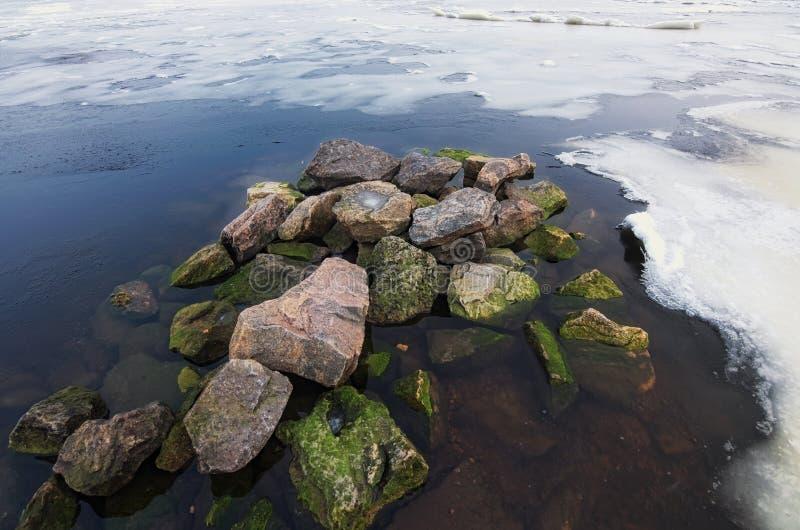 Los pedazos blancos del hielo y de la nieve con varias piedras en costa del río riegan por mañana fría del invierno foto de archivo libre de regalías