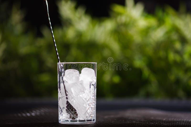 Los pedazos cuadrados grandes de hielo puro en un florero de cristal con una cuchara se colocan en la tabla contra la perspectiva imagen de archivo libre de regalías