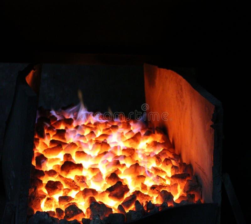 Los pedazos de carbón que queman en el cuerno del ` s del forjador fotografía de archivo