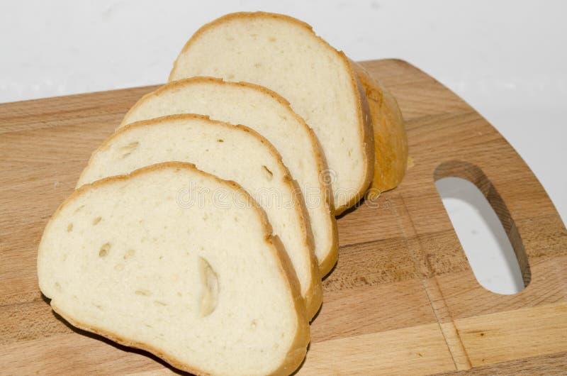 Los pedazos de pan en una tajadera imagenes de archivo