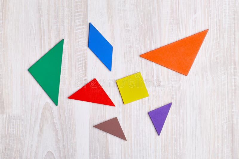 Los pedazos del color de rompecabezas se dispersan en un backgroun de madera ligero foto de archivo