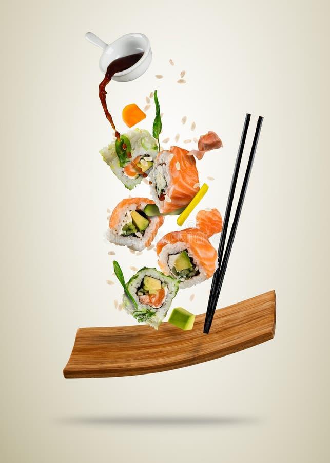 Los pedazos del sushi del vuelo sirvieron en la placa de madera, separada en vagos suaves ilustración del vector