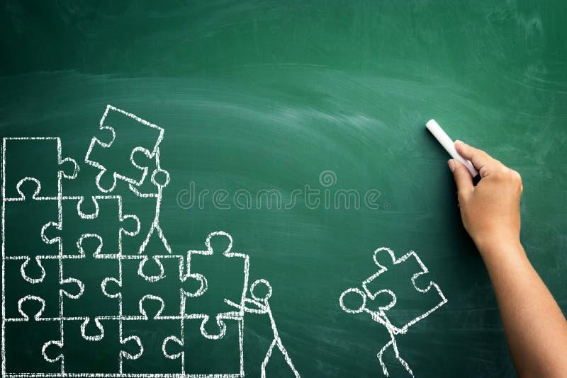 Los pedazos del trabajo en equipo y del rompecabezas con la persona firman encima la pizarra imagen de archivo libre de regalías