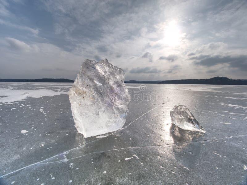 Los pedazos quebrados de hielo grueso sobre el lago congelado brillan en sol imagen de archivo