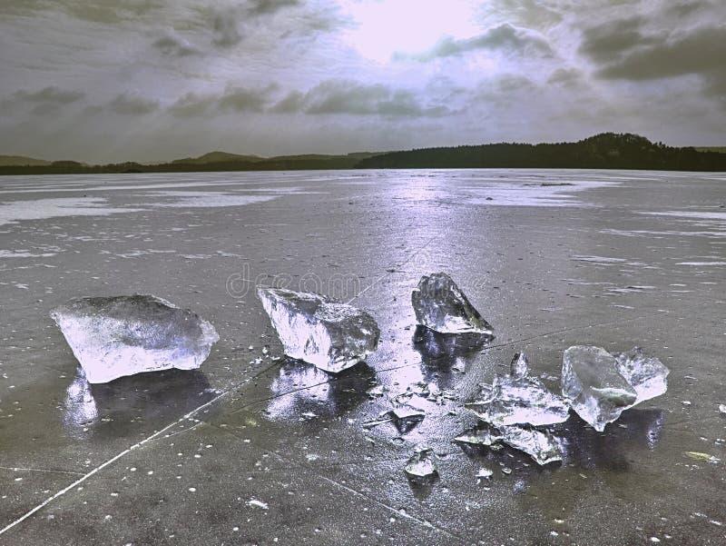 Los pedazos quebrados de hielo grueso sobre el lago congelado brillan en sol fotografía de archivo