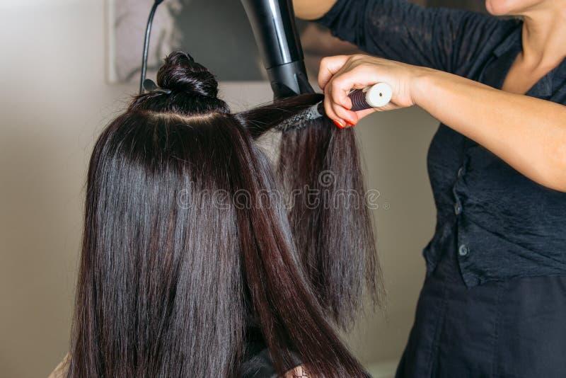 Los peluqueros dan el pelo negro largo de sequía con el secador del soplo y el cepillo redondo La cara modelo del ` s se cubre co fotos de archivo libres de regalías