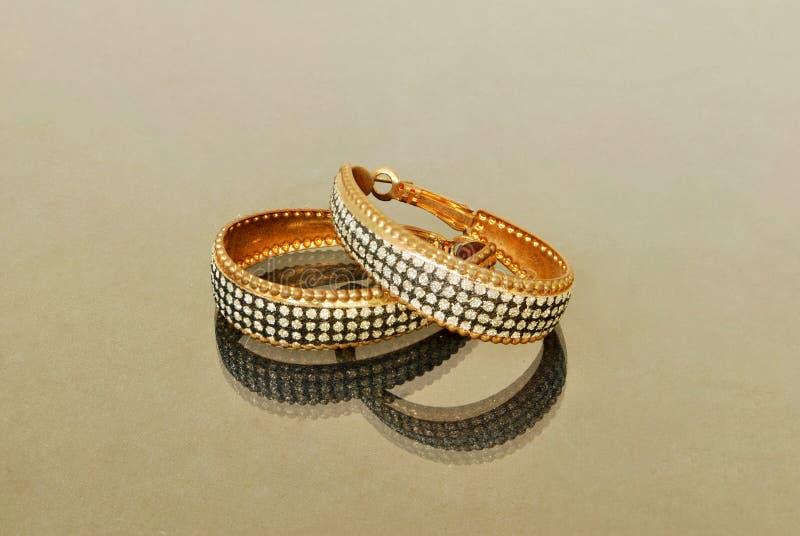 Los pendientes de las mujeres son diamante mezclado del oro imagen de archivo libre de regalías
