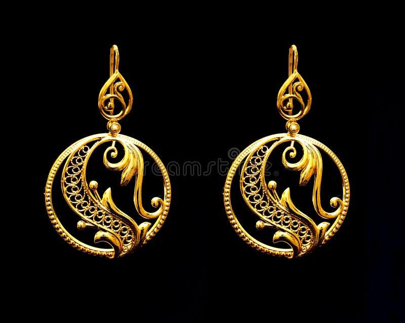 Los pendientes turcos del ` s de las mujeres de la joyería del oro oriental hermoso ennegrecen el fondo fotografía de archivo