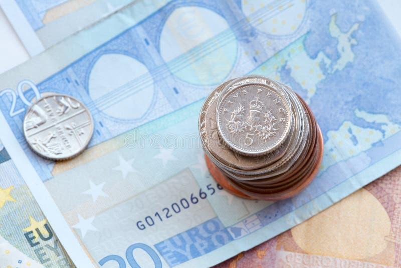 Los peniques de Reino Unido cinco acuñan en una pila de monedas fotografía de archivo libre de regalías