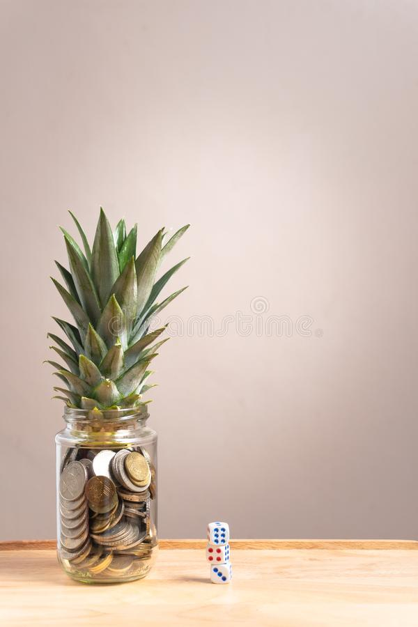 los peniques en la botella de cristal con la piña hojean en la parte superior y cortan en cuadritos en el otro lado fotos de archivo libres de regalías