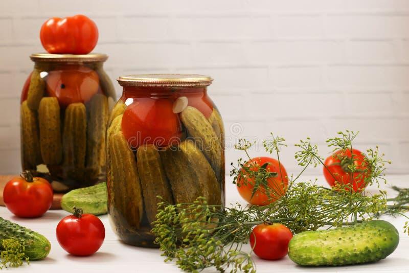 Los pepinos adobados con los tomates están situados en los tarros de cristal en un fondo blanco, cosecha para el invierno, foto h foto de archivo