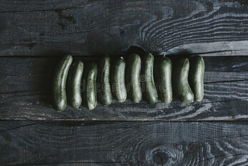 Los pepinos reman en la madera foto de archivo