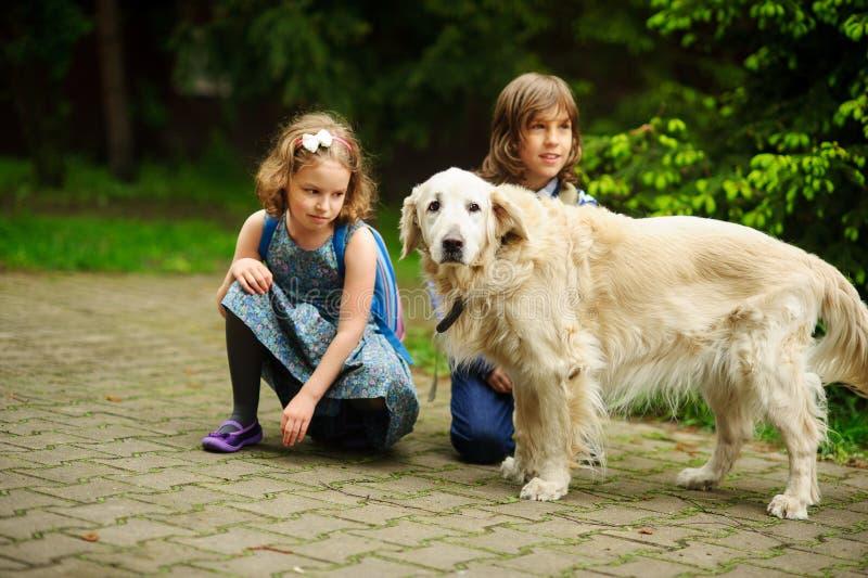 Los pequeños alumnos resolvieron en la manera a la escuela un perro grande imágenes de archivo libres de regalías