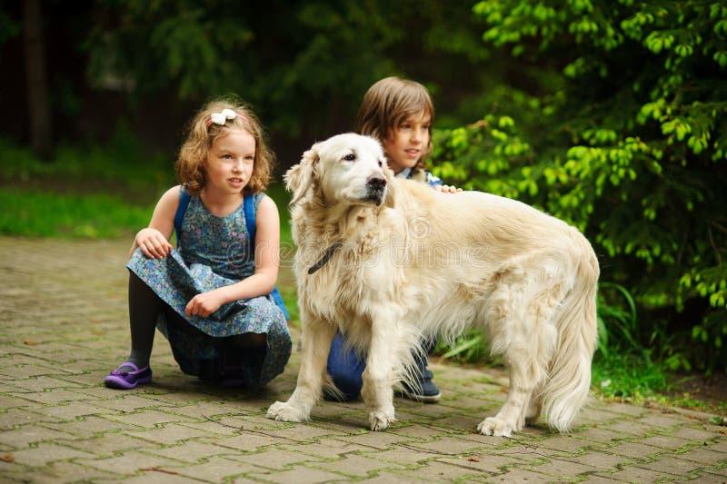 Los pequeños alumnos resolvieron en la manera a la escuela un perro grande foto de archivo libre de regalías