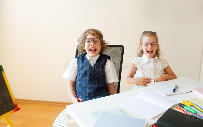 Los pequeños estudiantes ridículos con gafas, el muchacho y la muchacha, comparten el mismo escritorio imágenes de archivo libres de regalías