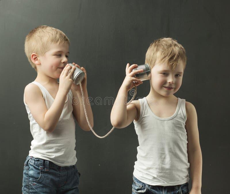 Los pequeños hermanos lindos que hablan en el juguete llaman por teléfono fotos de archivo libres de regalías