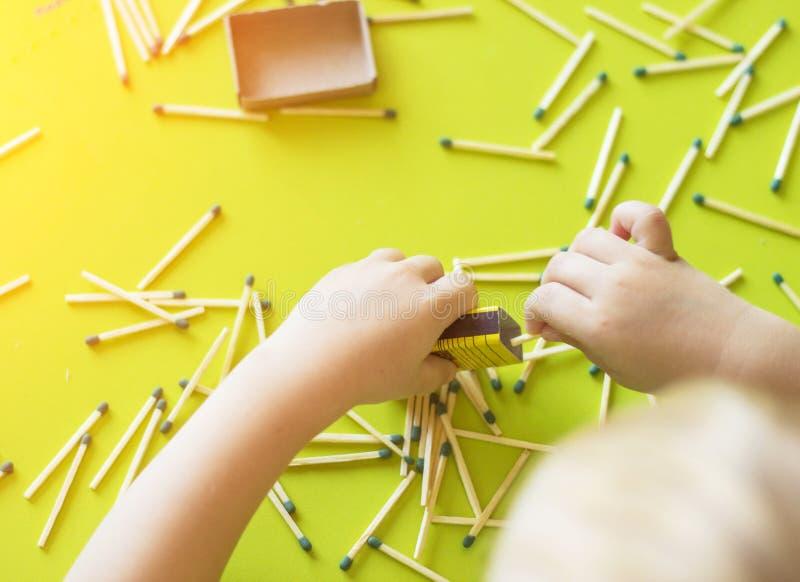 Los pequeños juegos de niños con los partidos, hacen juego partidos en las cajas, primers, fuego, partido del lucifer, mano fotos de archivo libres de regalías