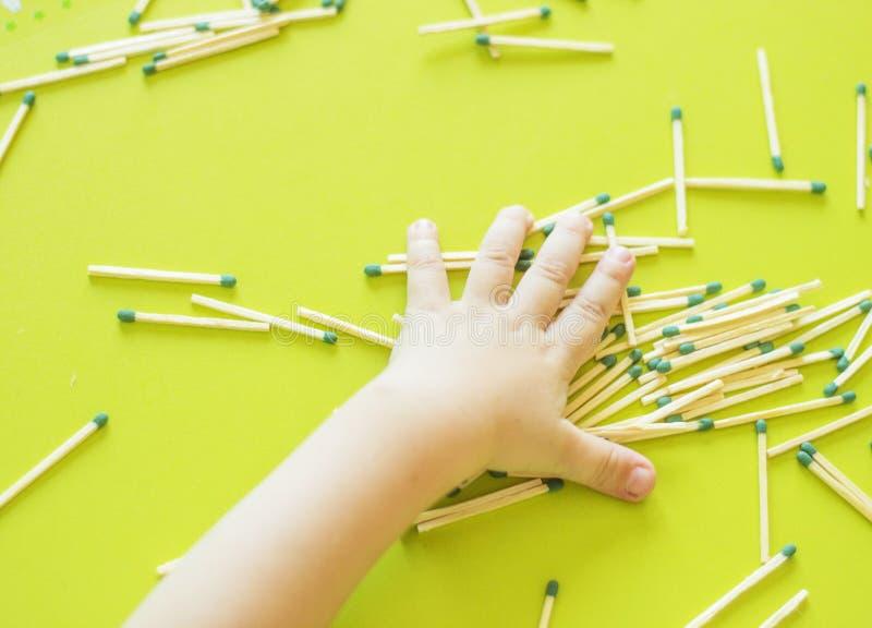Los pequeños juegos de niños con los partidos, una mano del ` s del niño toman partidos de la tabla, un primer, un fuego, partido foto de archivo libre de regalías
