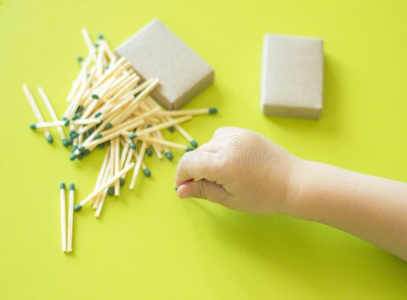 Los pequeños juegos de niños con los partidos, una mano del ` s del niño toman partidos de la tabla, un primer, un fuego, partido foto de archivo