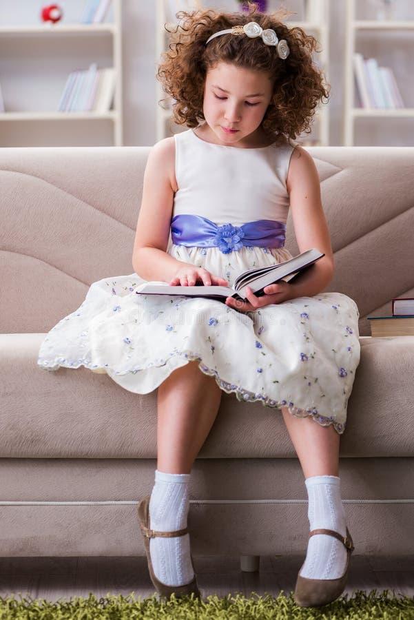 Los pequeños libros de lectura de la muchacha en casa fotografía de archivo libre de regalías