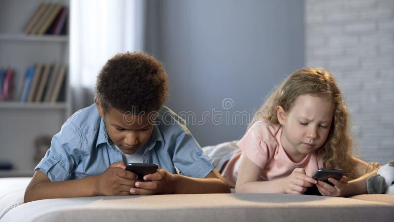 Los pequeños niños enviciaron a los teléfonos móviles que jugaban a juegos con las caras concentradas foto de archivo libre de regalías