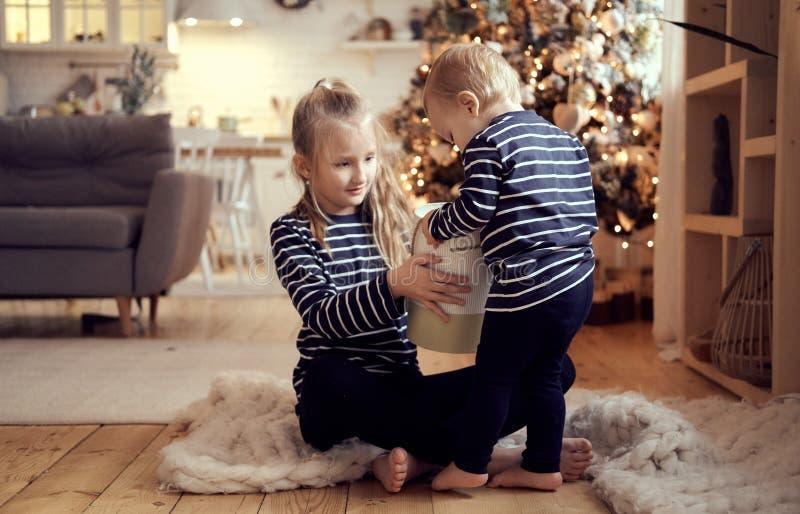 Los pequeños niños felices desempaquetan la caja de regalo foto de archivo libre de regalías