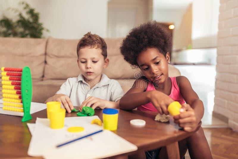 Los pequeños niños lindos moldean del plasticine en la tabla foto de archivo
