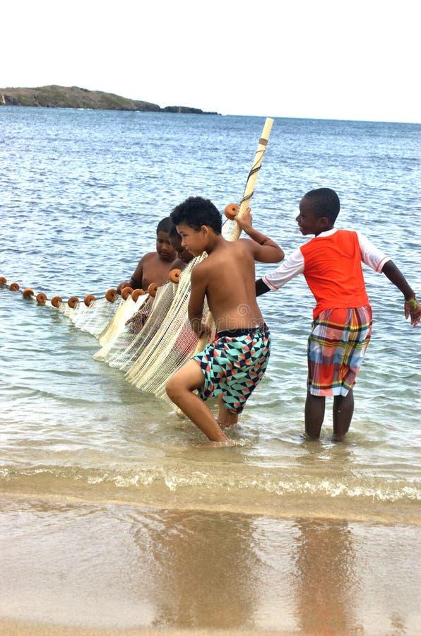 Los pequeños pescadores combinan con la red que intenta pescados cogidos fotografía de archivo
