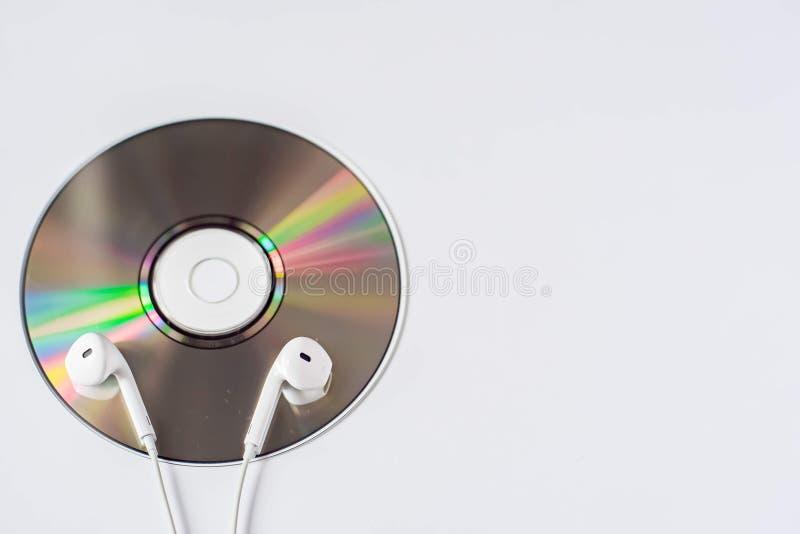 Los peque?os auriculares blancos est?n en el CD-ROM en el fondo blanco imagen de archivo