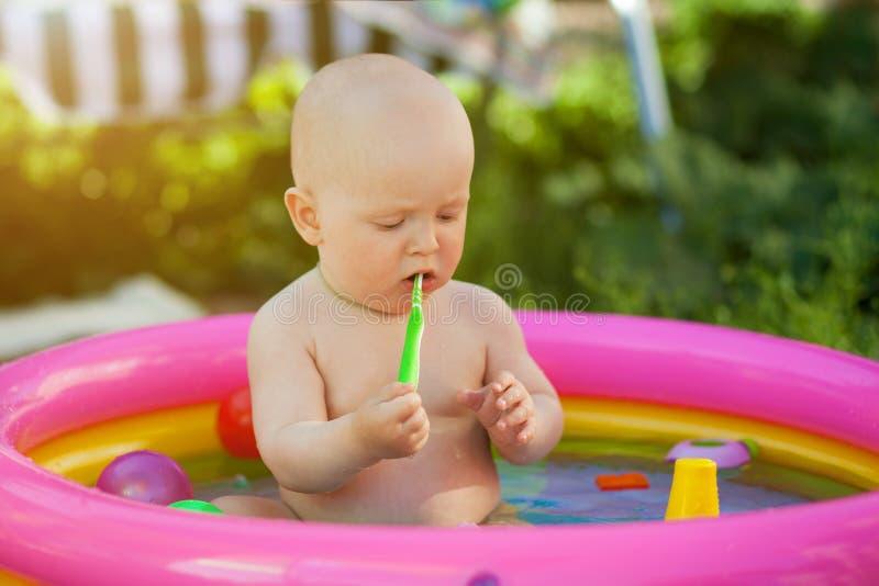 Los peque?os juegos de ni?os en una piscina inflable, aprenden nadar, jugando con los juguetes inflables coloridos fotos de archivo libres de regalías