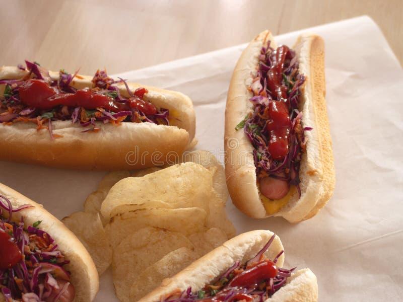 Los peque?os perritos calientes sirvieron con la mezcla de zanahoria Cole Slaw y de microprocesadores llanos foto de archivo libre de regalías