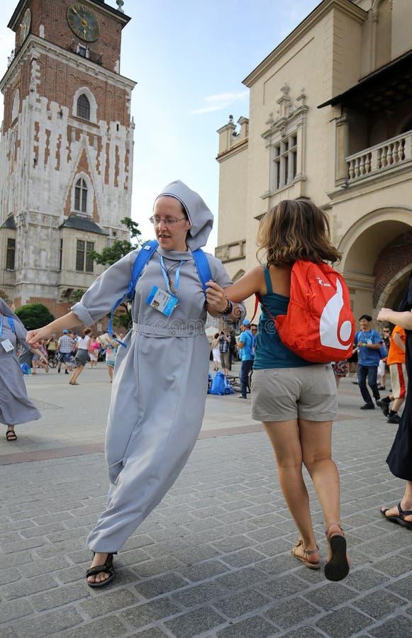 Los peregrinos del día de juventud de mundo cantan y bailan en la plaza principal en Cracovia imagen de archivo