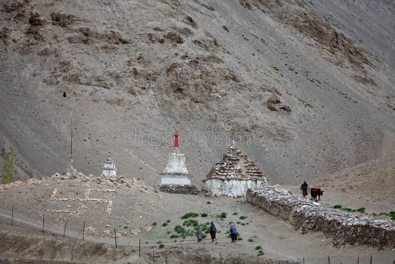 Los peregrinos que van a los stupas y la cruz gamada de piedra cruzan fotos de archivo