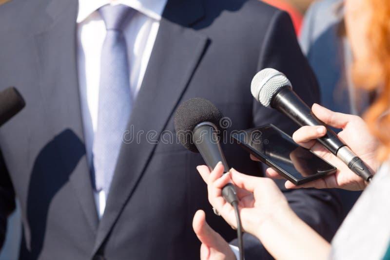 Los periodistas que hacen medios se entrevistan con con la persona o el pol?tico del negocio imagenes de archivo