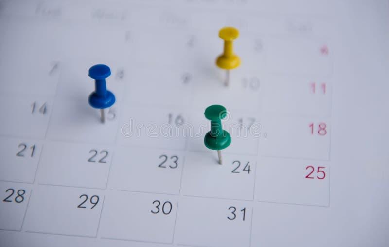 Los pernos coloridos del primer empujan la marca en un calendario Horario ocupado imagen de archivo