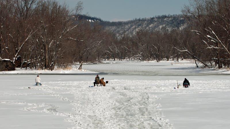 Los pescadores del hielo disfrutan de la sol caliente de marzo imagen de archivo