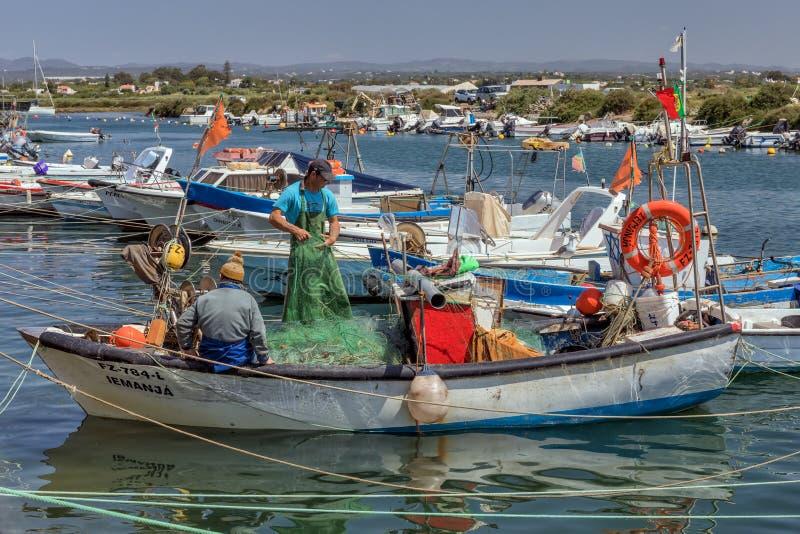 Los pescadores en su barco en Fuseta se abrigan, Algarve, Portugal foto de archivo libre de regalías