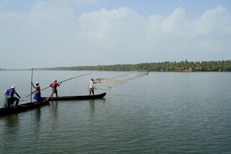 Los pescadores en un barco cogen pescados lanzando la red adentro a los remansos por una mañana brumosa imagen de archivo
