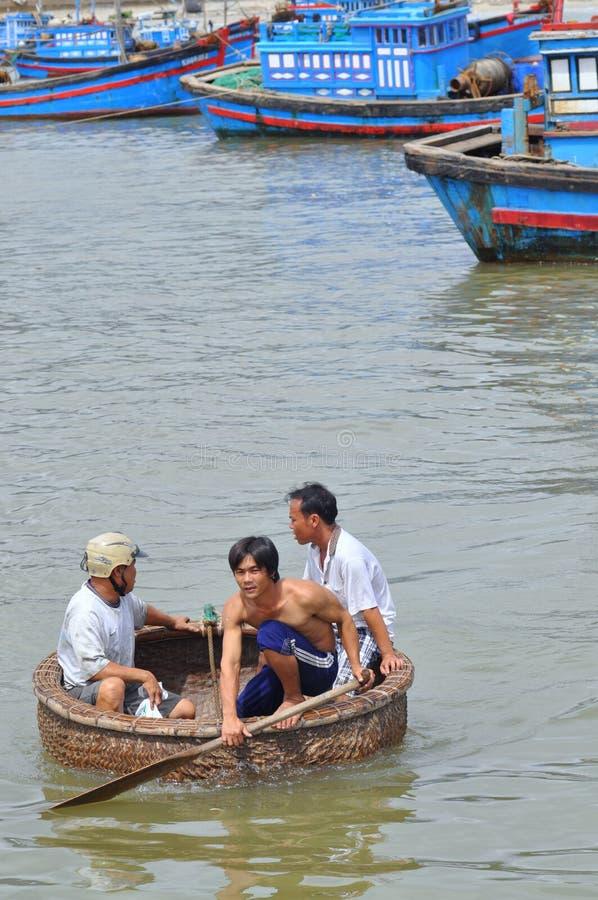 Los pescadores están nadando de sus buques al puerto en un barco de la cesta foto de archivo libre de regalías
