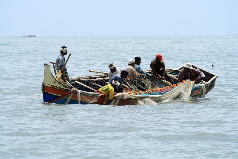 Los pescadores hacen la pesca usando el barco y la red de pesca fotos de archivo